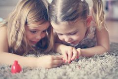 Girl stuff. Sisters have play together. Two little girls painted their nails at home. Close up image Royalty Free Stock Photos