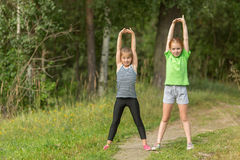 Two little girls perform gymnastic exercises outdoors. Sport. Stock Photo