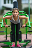Two little girls perform gymnastic exercises outdoors. Sport. Stock Photos