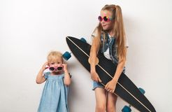 Two little girls in pink sunglasses and jeans clothes on a white background. The elder sister is holding a long board Stock Photos