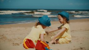 Two little girls play on the beach in summer. Two little and cute girls play on the beach by the sea in summer stock video