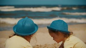 Two little girls play on the beach in summer. Two little and cute girls play on the beach by the sea in summer stock footage