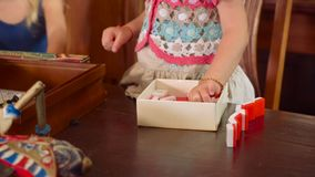 Two little girls play with board games. In wooden room stock video