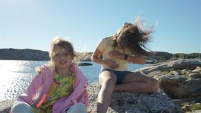 Two little girls play among the coastal rocks on the beach. Run, laugh and enjoy a Sunny day. Slow motion stock footage