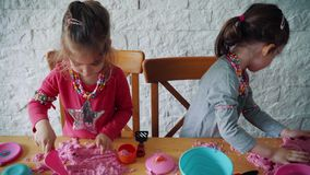 Two little girls play with kinetic sand on the table. Two lovely girls sit at the table and play with pink kinetic sand stock video footage