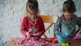 Two little girls play with kinetic sand on the table. Two lovely girls sit at the table and play with pink kinetic sand stock footage