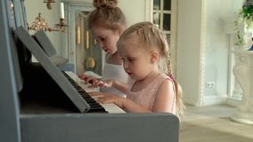 Two Beautiful Girls Play The Piano Stock Video - Video of