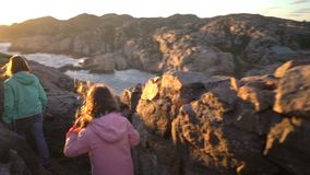 Two little girls play on a rocky northern seashore. Run, laugh, explore the coastal rocks and enjoy a great adventure. Slow motion