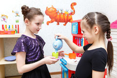 Two little girls play role game with toy kitchen in day care cen. Ter indoors Stock Photography