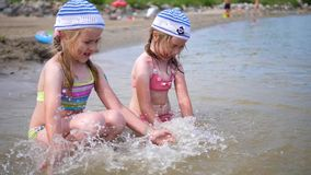 Two little girls play on the sea. Children poured water, create spray. Hot summer day, cheerful mood. Twins pour water on a hot summer day, laughter and good stock video