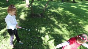 Two little girls play with soap bubbles in park. Two little girls play with soap bubbles in green summer park stock footage