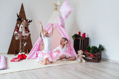 Two little girls play in a teepee. Two little girls, sisters, friends play in a tent in a house or teepee royalty free stock photography