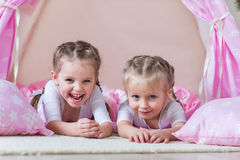 Two little girls play in a teepee. Two little girls, sisters, friends play in a tent in a house or teepee Royalty Free Stock Image