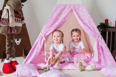 Two little girls play in a teepee. Two little girls, sisters, friends play in a tent in a house or teepee stock images