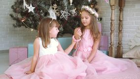 Two little girls play together and laugh near the Christmas tree. The girl has a wreath on her head, she in a beautiful dress decorates Christmas tree with stock video