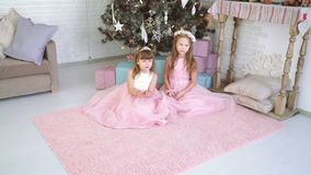 Two little girls play together and laugh near the Christmas tree. The girl has a wreath on her head, she in a beautiful dress decorates Christmas tree with stock footage
