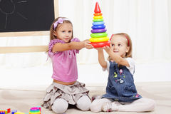 Two little girls play with toys Royalty Free Stock Photos