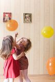 Two little girls playing with airy balls