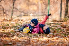The two little baby girls playing in autumn leaves. The two little girls playing with ball in the autumn leaves in park Stock Photography