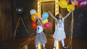 Two little girls playing with balloons. Best friends. Two cute little girls holding balloons stock footage