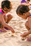 Two little girls playing beach sands Stock Photos