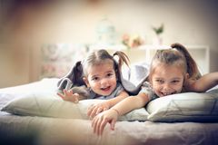 Two cheerfully little girls in bed. Two little girls playing in bed. Space for copy royalty free stock photography