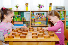 Two little girls playing in checkers. In kindergarten stock image
