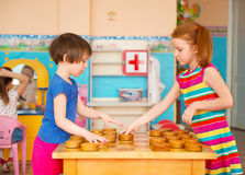 Two little girls playing in checkers at kindergarten Stock Images