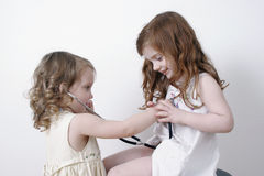 Two little girls playing doctor. Toddler girl listening to another little girls heart with a stethoscope Stock Image