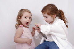 Two little girls playing doctor. Cute little girls with a white doctor's coat and a tongue depressor Stock Photos