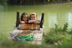 Two little girls playing in the farm lake Stock Image