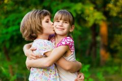 Two little girls playing fly in summer park. Concept of family. stock photos