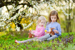 Two little girls playing in a garden on Easter Stock Photos