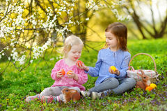 Two little girls playing in a garden on Easter Royalty Free Stock Images