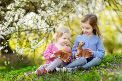 Two little girls playing in a garden on Easter Stock Image