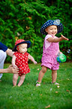 Two little girls playing on the green grass in spring garden Royalty Free Stock Photo