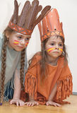 Two little girls playing Indians. Two sisters dressed as Indians on the floor Stock Photography