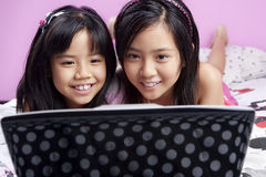 Two little girls playing with laptop Stock Photo