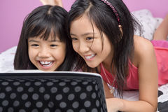 Two little girls playing with laptop Royalty Free Stock Photography