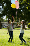 Two little girls playing outdoors. With colorful balloons Stock Photography
