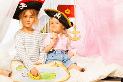 Two little girls playing pirates with treasure map. Two little girls wearing three-cornered hats, playing pirates, looking for treasures with old map Stock Photos