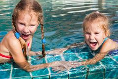 Two little girls playing in the pool stock photography