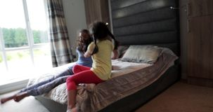 Little Girls Playing in the House. Two little girls playing, running in the house and jumping onto the bed stock video footage
