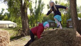 Two little girls playing in spring outdoor on a haystack. Slow motion stock video