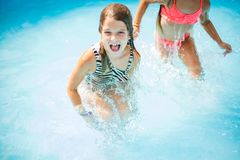 Two little girls playing in pool. royalty free stock photo