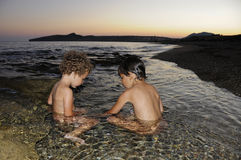 Two little girls playing in water at seaside. At dusk Royalty Free Stock Photos