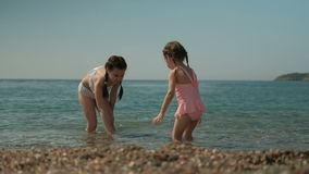Two little girls are playing in the water on the sunny beach. The adult sister splashes slightly. Together, children have a good time during the holidays stock footage