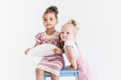 Two little girls playing on a white background royalty free stock photo