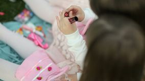 Two little girls are playing with children`s cosmetics on a green meadow. little women of fashion. Two little girls are playingwith children`s cosmetics on a stock video footage