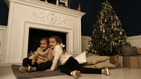 Two little girls pose during Christmas photo session. Studio shooting before the holidays. stock photography